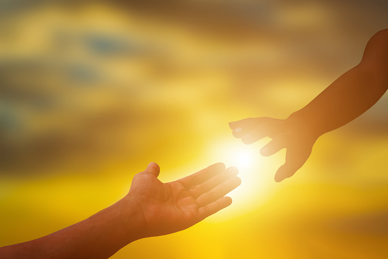 Silhouette of helping hand at sunset,please help me.helping and teamwork concept.
