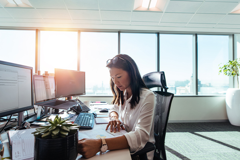 Businesswoman studying business papers on her desk. Woman working in office sitting at her desk.